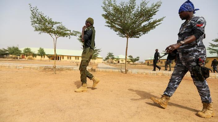 Des policiers marchent devant l'école JSS Jangebe, un jour après l'enlèvement de plus de 300 écolières par des bandits, à Zamfara, au Nigeria, le 27 février 2021.
